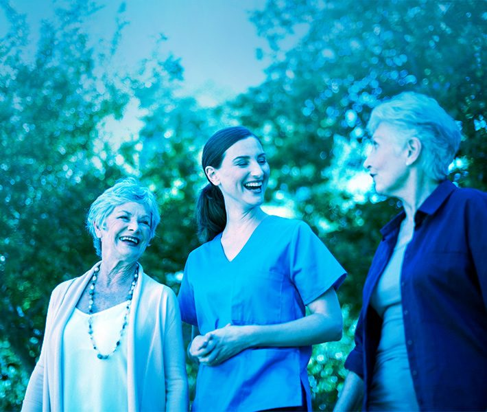 a young nurse laughing with two older women
