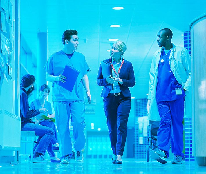 three healthcare professionals talking while talking down a hallway
