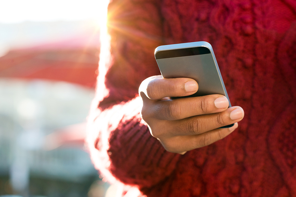 A person in a red sweater holding a smart phone.