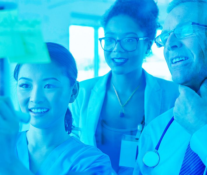 three healthcare professionals looking at a whiteboard