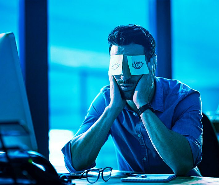 a man sitting at his desk with his head in his hands and sticky notes covering his eyes