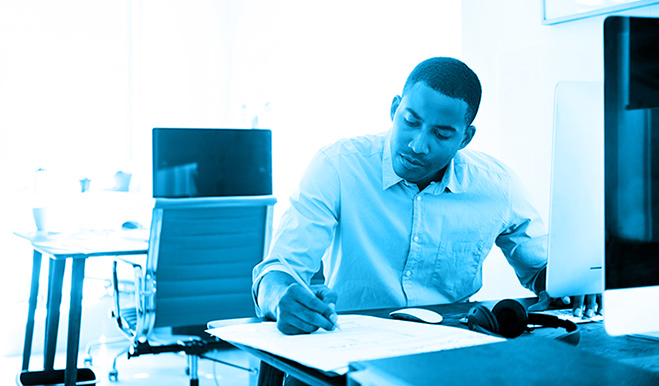 a man working at a desk and writing something down on a piece of paper