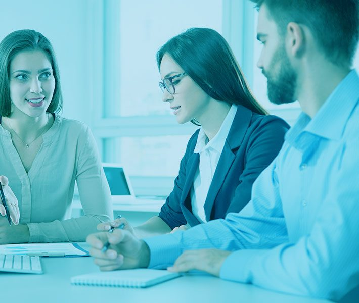 three people in business casual clothes in a meeting